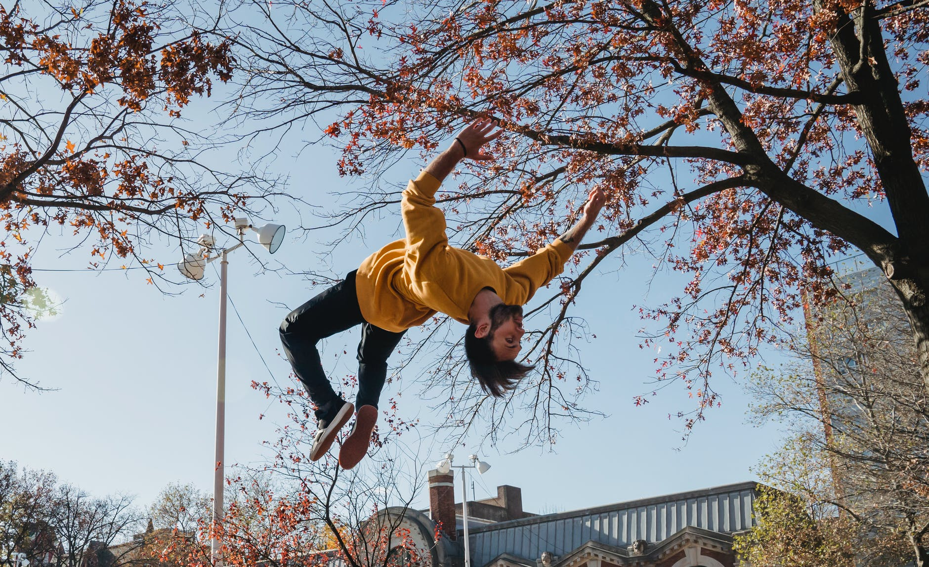 guy doing backflip in city park
